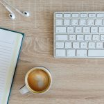 teclado de computador, cuaderno, audífonos y capuchino sobre un escritorio de madera. fuero de maternidad en desempleo