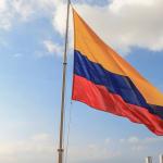 bandera de colombia izada con el cielo azul de fondo. Elecciones beneficios y obligaciones laborales