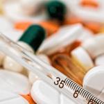 variedad de pastillas y un termómetro. pago de incapacidades