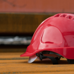 casco de protección color rojo sobre un banco de madera. terminación de contrato trabajador discapacitado