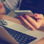 mujer revisando su smartphone mientras tiene el computador portatil abierto. empleador conoce embarazo de trabajadoras