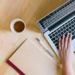 sobre un escritorio de madera hay unas manos en el teclado de un computador portatil. una taza de cafe, un cuaderno y un bolígrafo. fechas reporte sena variacion trabajadores