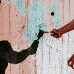 persona pintando de azul una cerca de madera. trabajo voluntario no es remunerado