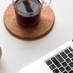 taza de café, teclado de un computador portátil y una planta suculenta sobre un escritorio. ministerio de salud y protección social define medidas bioseguridad