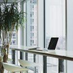 Mesa de bar con computador portatil, una planta y una silla de bar, de fondo hay una ventana de altura piso-techo. ministerio de trabajo ejercerá preferente por Coronavirus