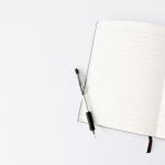 Cuaderno abierto, lapicero negro sobre superficie. Estrategia sacúdete: gobierno subsidiará 25% de salario mínimo para jóvenes, roes abogados